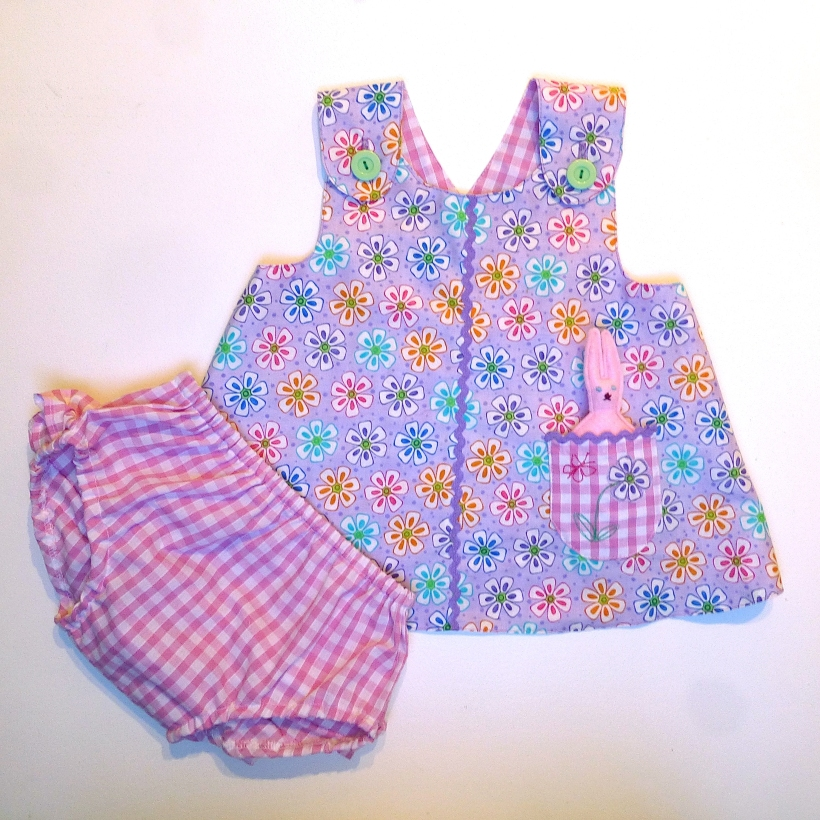 baby wrap over dress and frilly pants with toy rabbit
